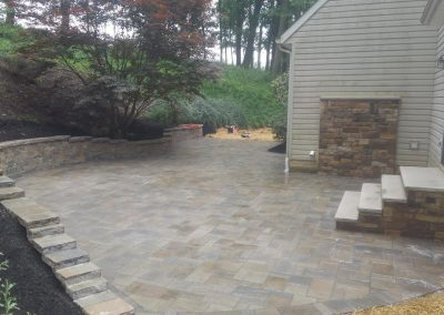 Interlocking stonework patio and retaining wall built into hillside by Frederick Landscaping Maryland