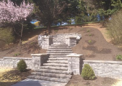 Retaining wall with stone staircase leading to fire pit built into hillside
