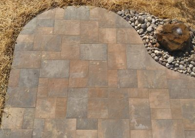 Curved patio constructed with Belgard Origins 18 Pavers with adjacent boulder bubbler fountain water feature