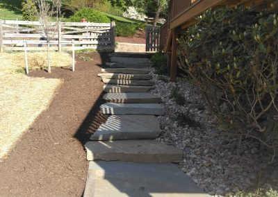Colonial natural stone steppers connecting patio and driveway