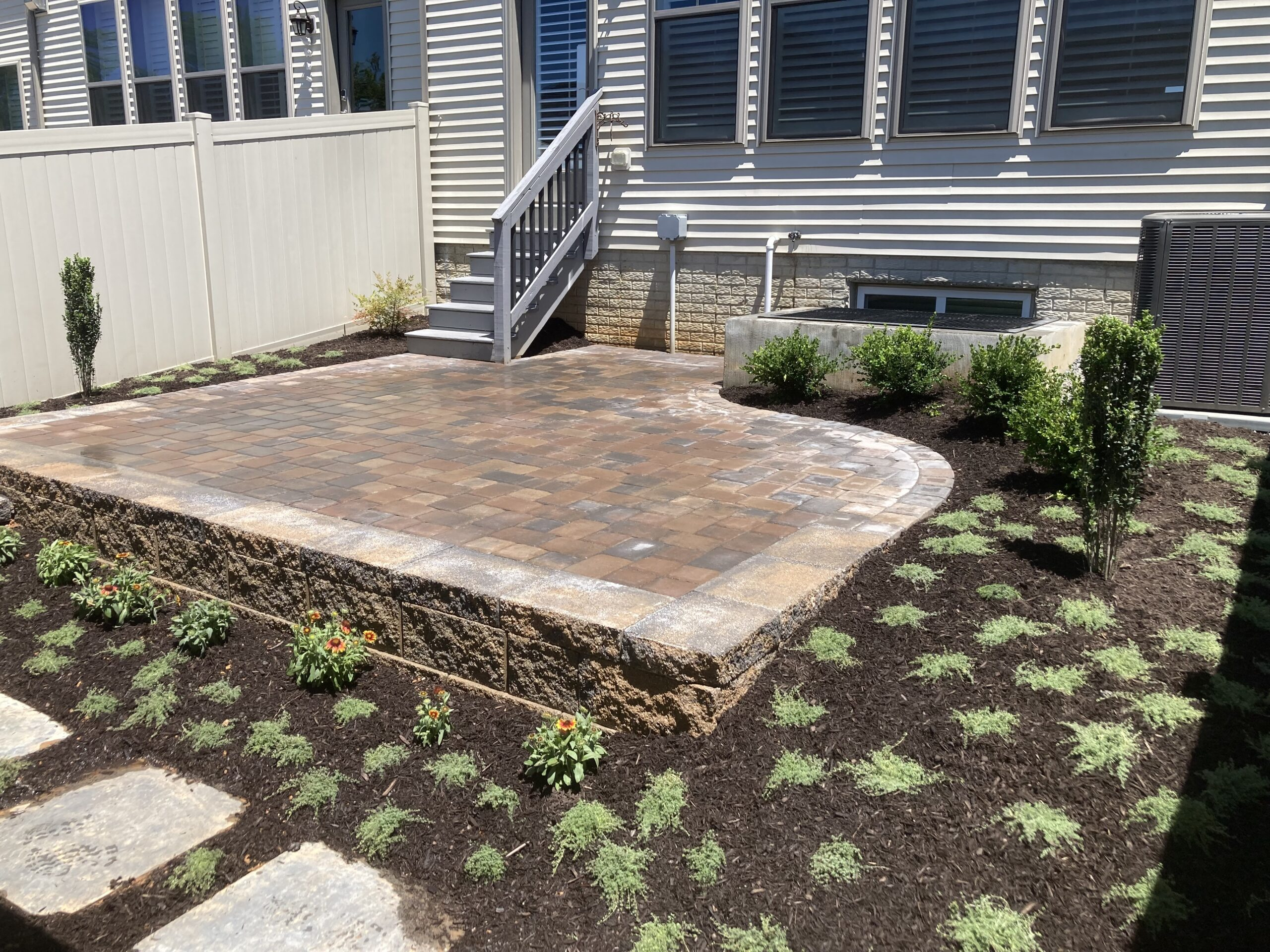 Row home backyard landscaped with Belgard pavers, shrubs and flowers