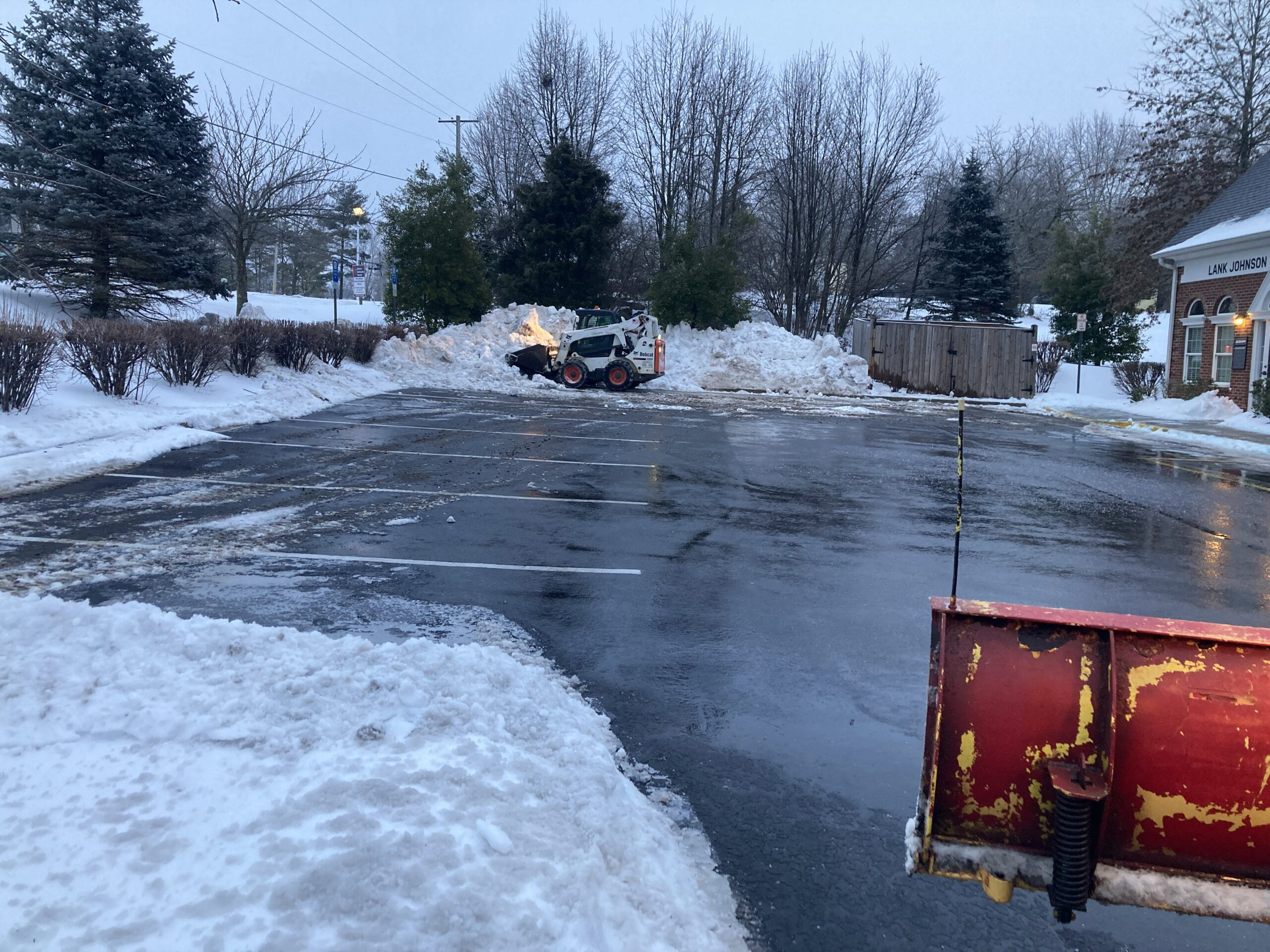 Snow being removed from commercial parking lot by bobcat machine
