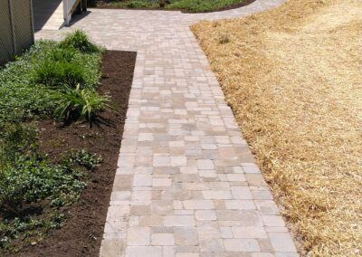 beautifully paved walkway leading up to wheelchair ramp and extending around house